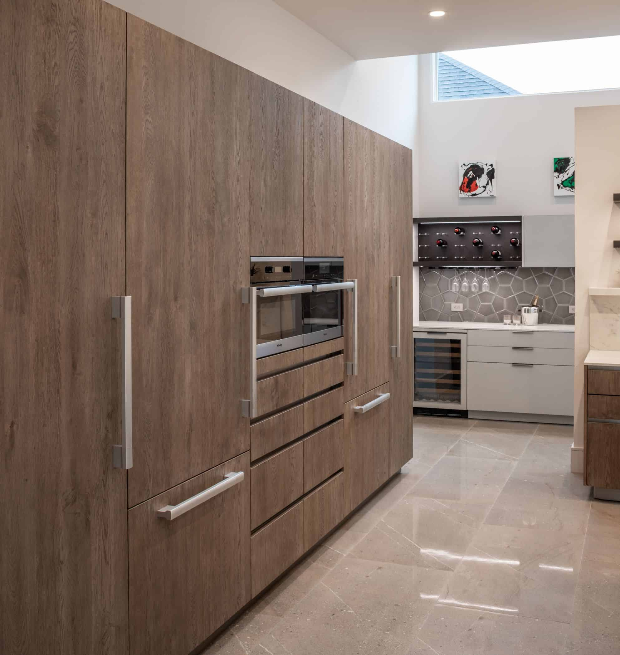 integrated appliance wall and hidden pantry in german cabinetry of a washington coalition memorial park area home in houston