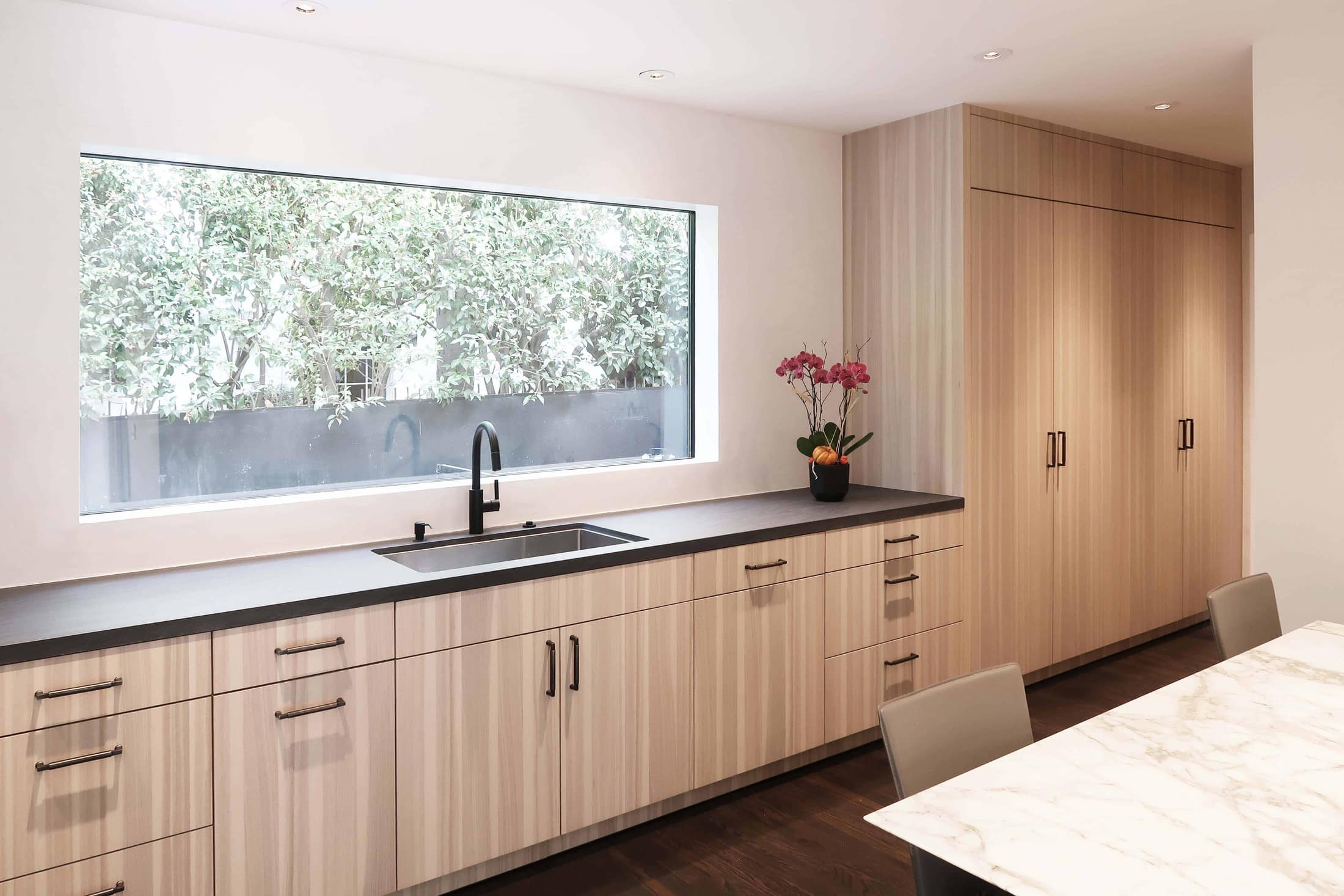 after picture of the sink and exterior window of a modern eggersmann kitchen with traditional touches created in a hancock park traditional home in los angeles