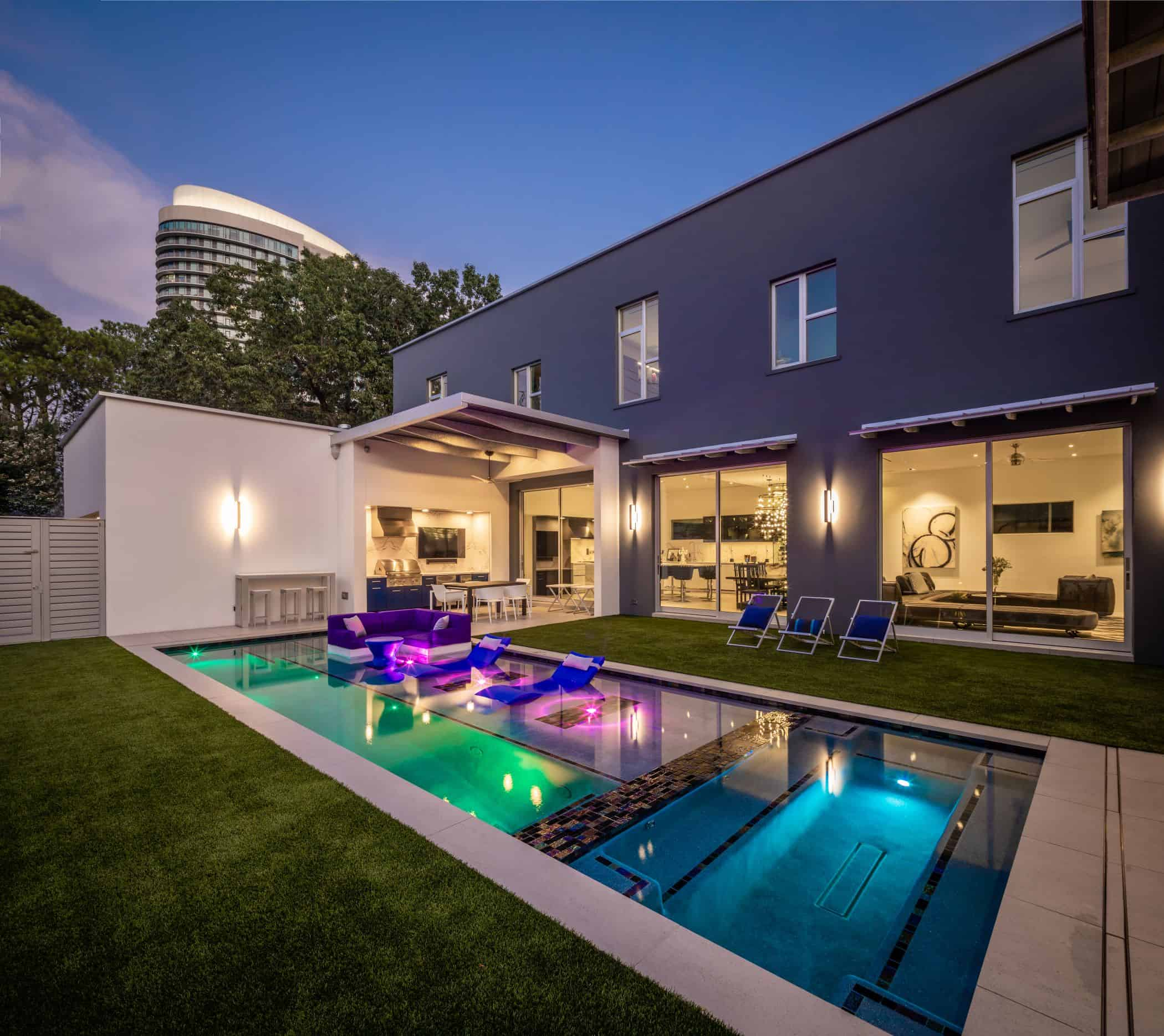 ultra modern pool lit at dusk behind a newly built home in upper kirby