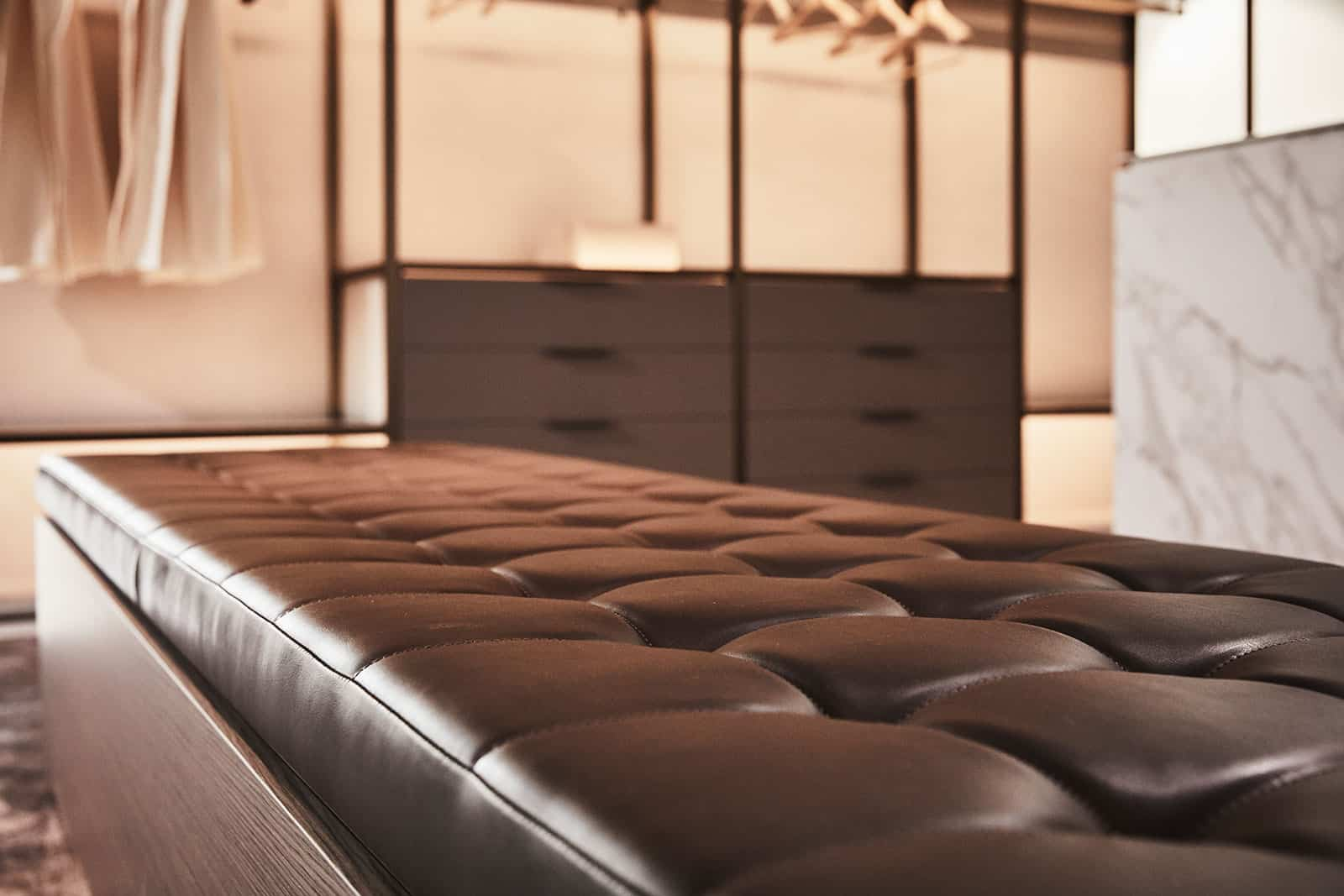 tufted leather bench makes a statement and a place to put your shoes on in a schmalenbach luxury closet