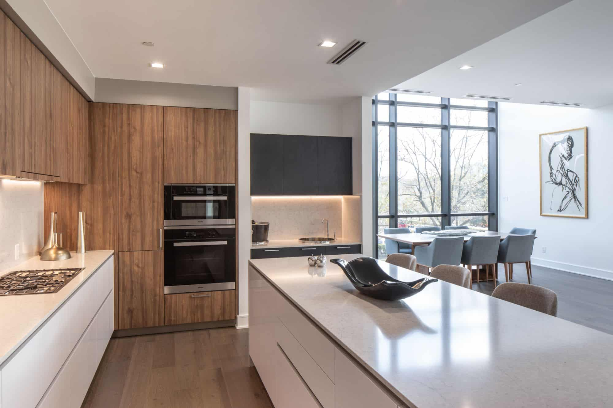 Luxury solid surface kitchen with natural light wood accents amplifies the natural light from the floor to ceiling windows