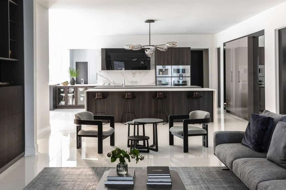 luxury kitchen and living room with light streaming in from ample windows