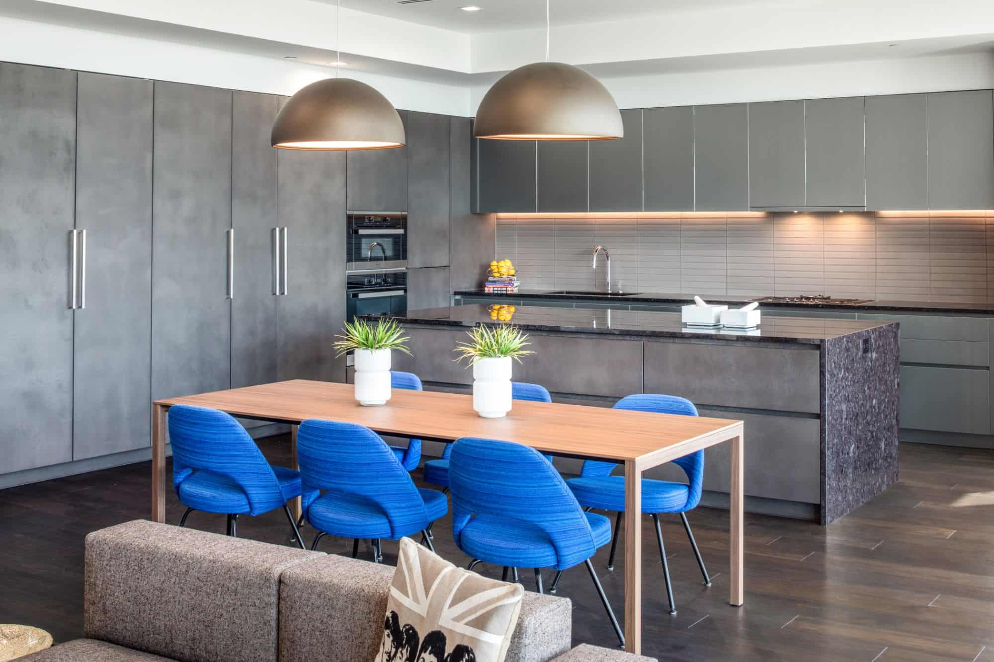 mid to dark tones of gray on gray in this kitchen by eggersmann are beautifully accented by the bright peacock blue custom dining chairs