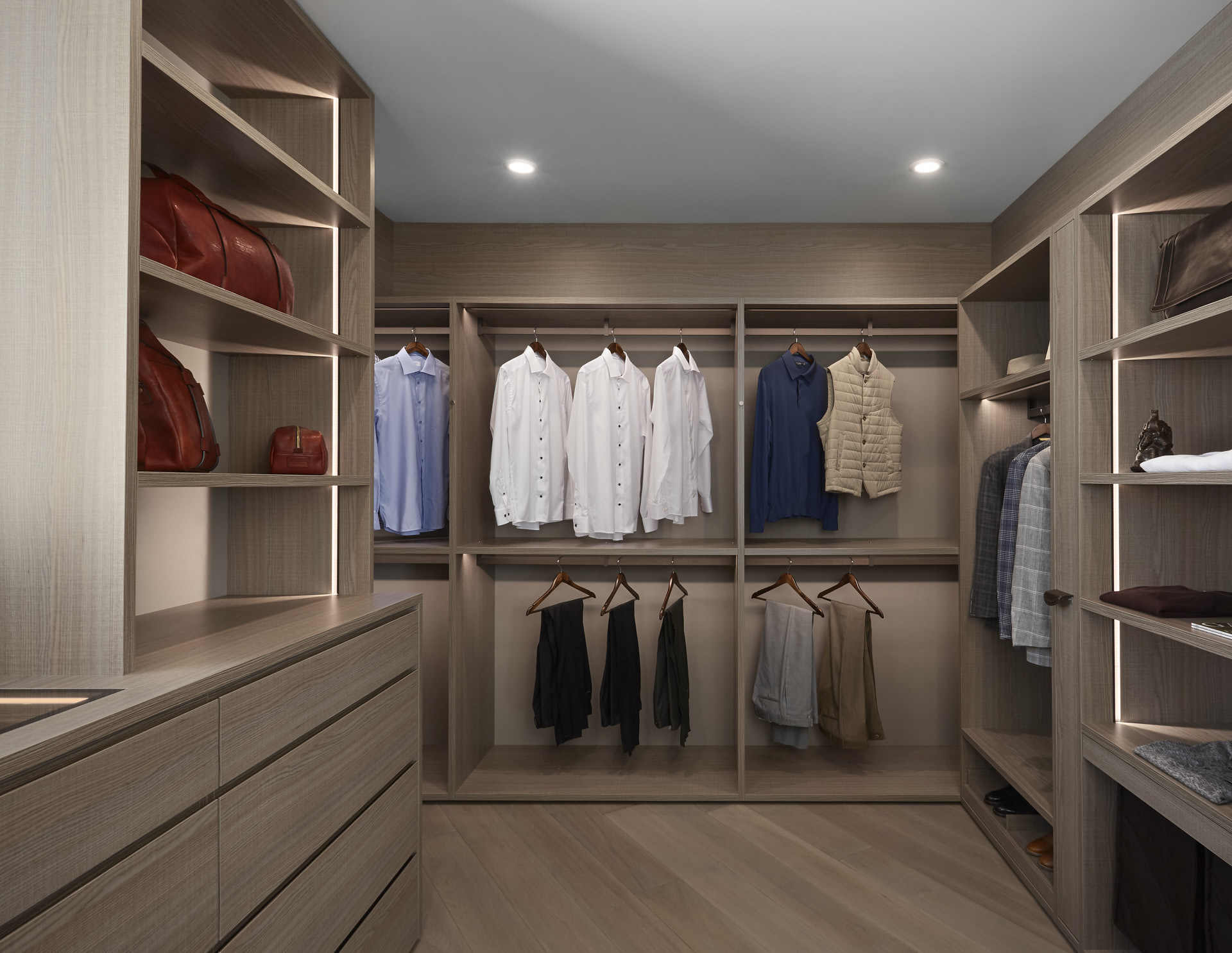 bespoke walk-in wardrobe using mid-tone finishes to achieve a masculine beachy feel