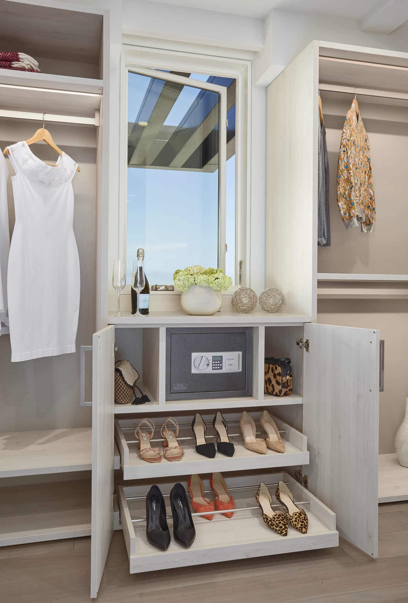custom shoe storage and safe below a large window overlooking the pacific ocean