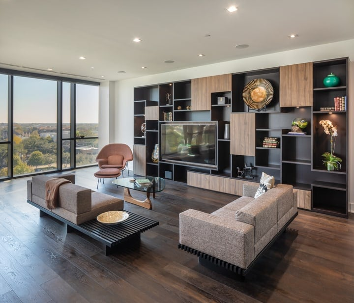 living area featuring a custom media unit with shelves and storage in unit 601 at the mond luxury condos