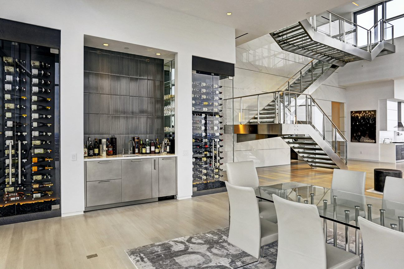 dining room and elaborate high end bar and wine rooms of the east penthouse in the 2727 kirby luxury high rise condos in houston