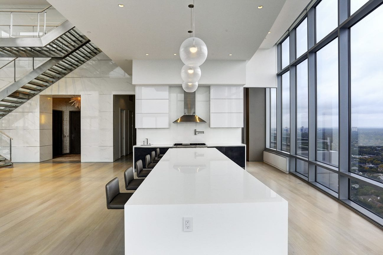 expansive waterfall counter island in white quartz glass with seating for 10 designed by eggersmann for the east penthouse in the 2727 kirby luxury high rise condos in houston