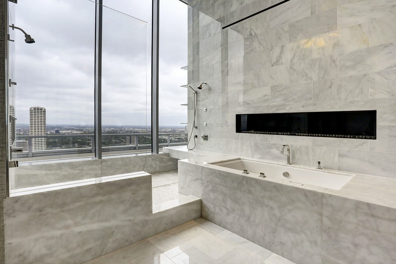 master bath shower and tub with fireplace of the east penthouse in the 2727 kirby luxury high rise condos in houston