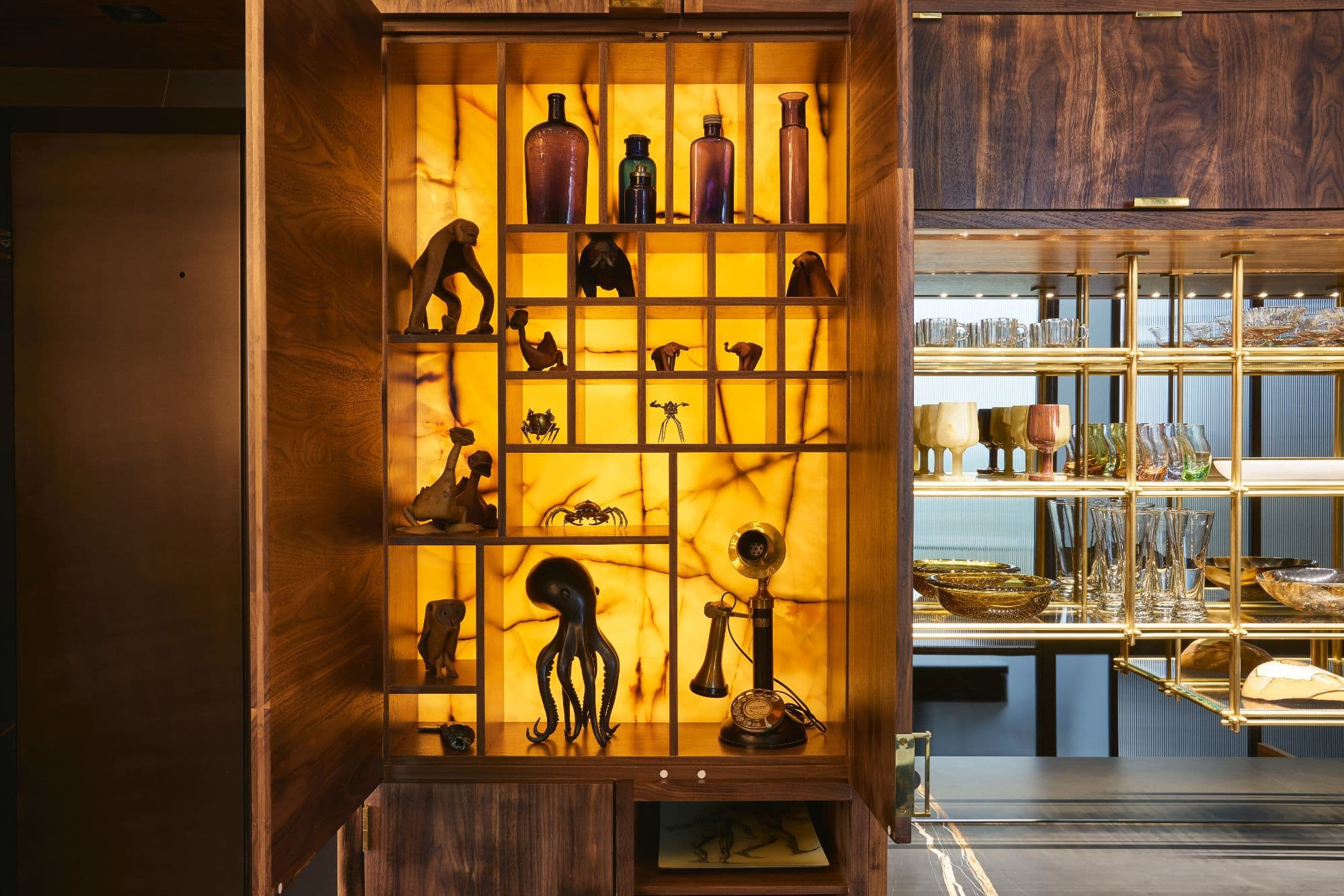 eclectic small sculpture collection in a backlit cabinet featuring an amber glow inside a penthouse of the arabella luxury high rise in houston