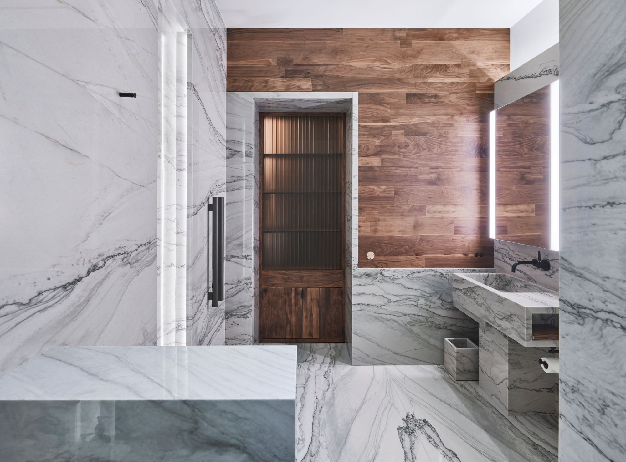 luxury bathroom featuring classic white marble and a warm wood plank accent wall inside a penthouse of the arabella luxury high rise in houston