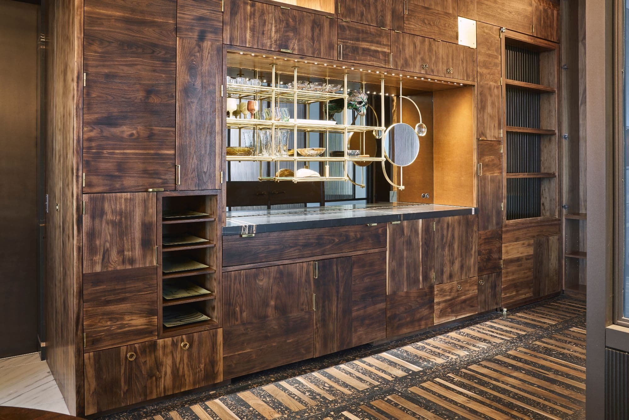 custom cabinetry providing a bar and ample storage in the hallway area inside a penthouse of the arabella luxury high rise in houston