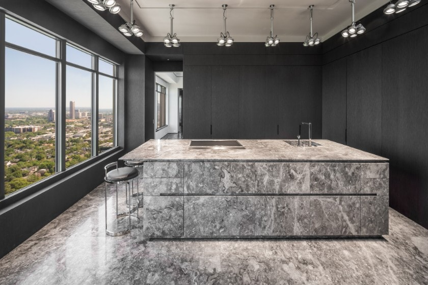 straight-on view of island and hidden wall cabinet storage in a luxury kitchen in the huntingdon luxury high-rise on kirby in houston