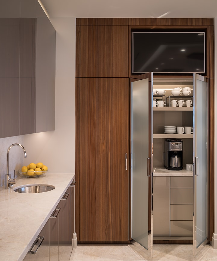 coffee bar behind glass doors in custom-designed kitchen in the belfiore high-rise luxury condos