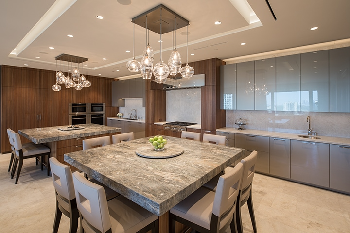 custom double-island kitchen featuring wood, stone, and sleek glass finishes in an eggersmann kitchen in belfiore condos in houston