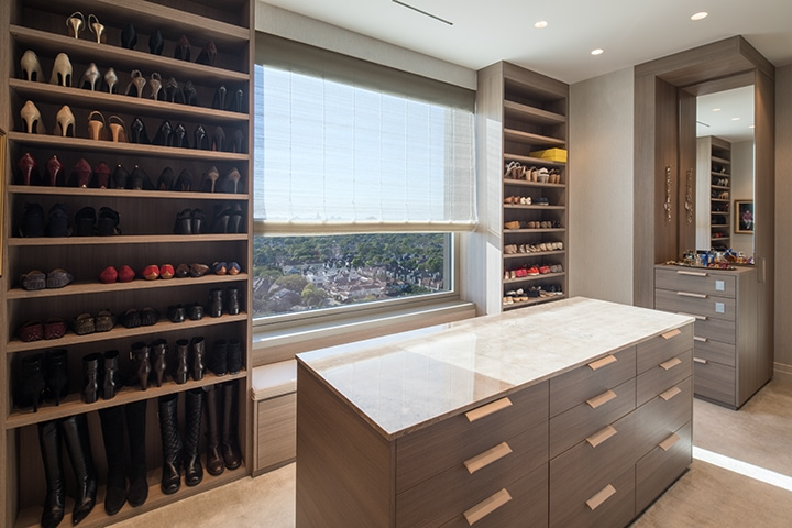 storage galore with island and custom shelving in a Schmalenbach closet for her