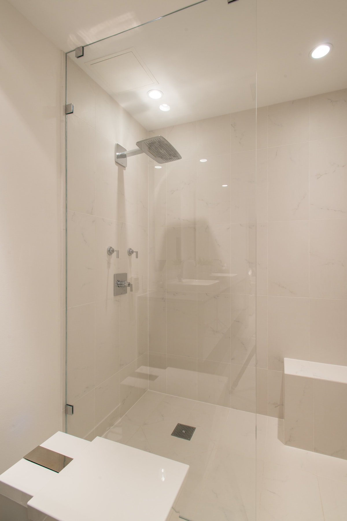 whilte marble shower with glass wall keeps the space clean and airy