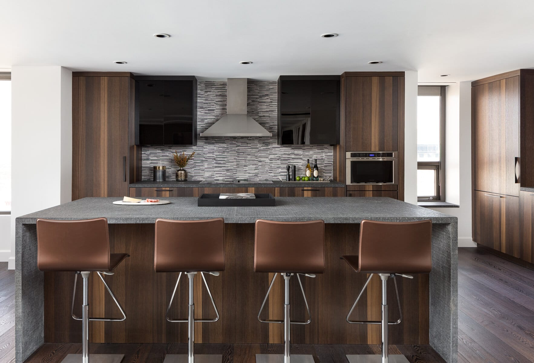 Entertaining Island with a Backdrop of Custom Hood and Black Glass Fronts