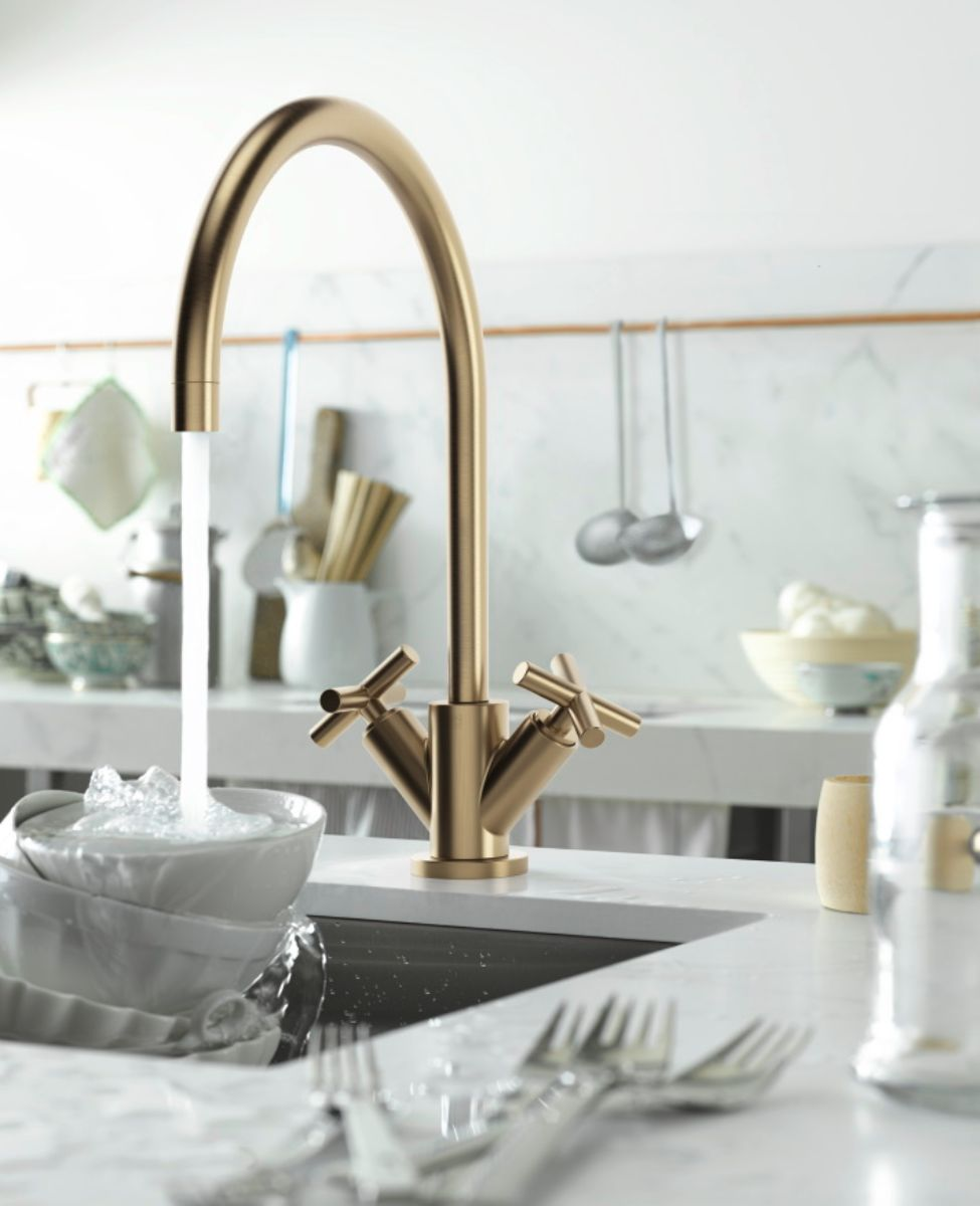 luxury gold faucet with double angled handles and gooseneck in an eggersmann kitchen
