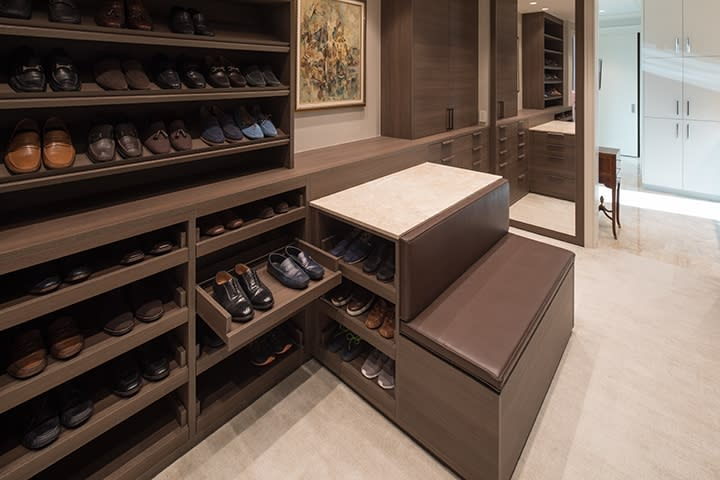 shoe storage with peninsula featuring a custom bench in a Schmalenbach closet for him