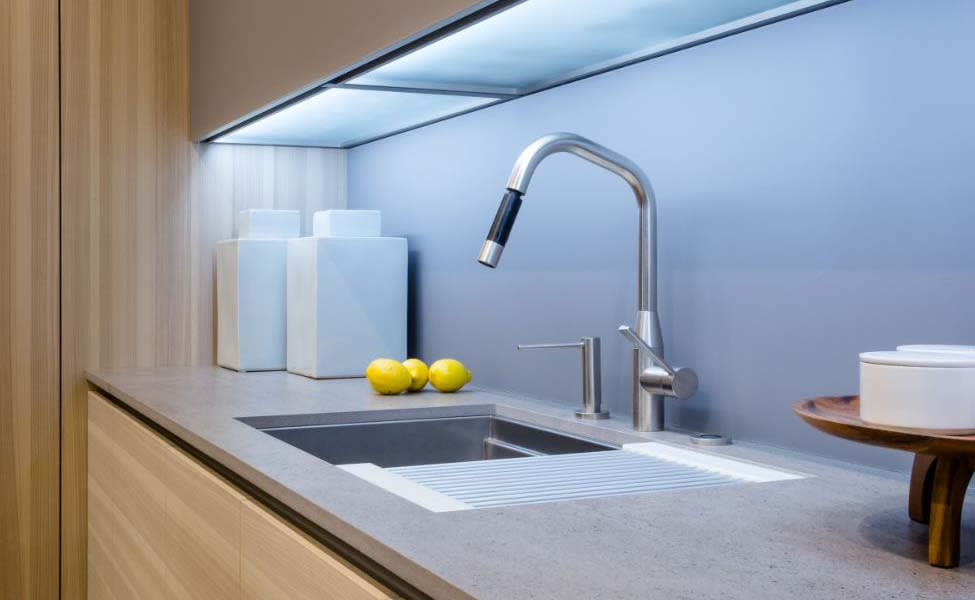 high-end kitchen faucet and soap dispenser with stylized gooseneck design and sleek pull-out sprayer designed by dornbracht