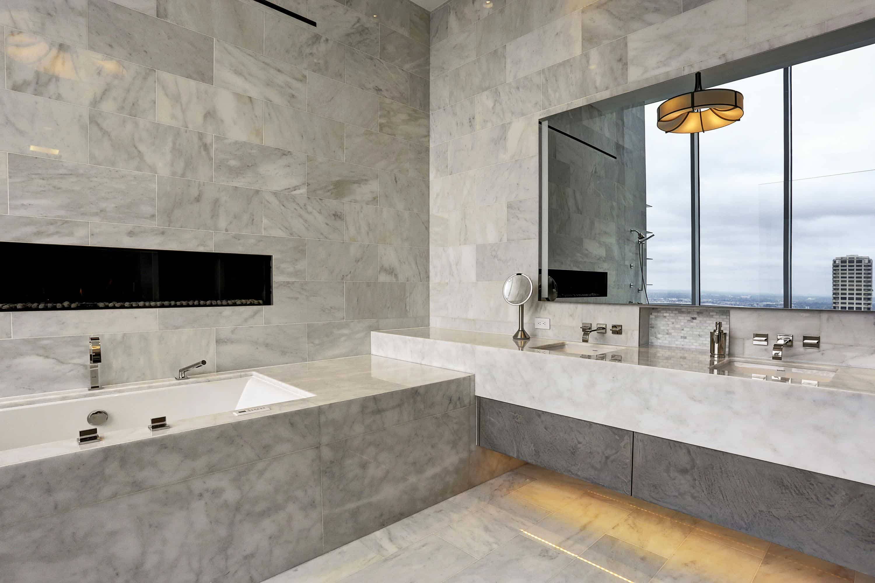 eggersmann design for this bathroom includes stone, stone, and more stone to accent the highrise city view and cozy ultra modern fireplace above the tub