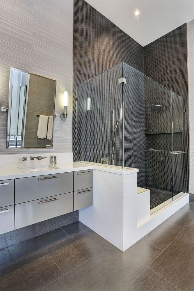 floating gloss gray vanity abuts corian clad shower wall in an eggersmann-designed bathroom in this luxurious modern home