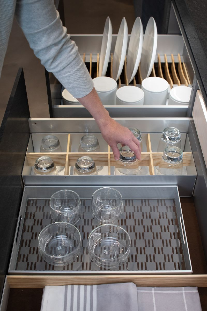 woman selecting a glass from an eggersmann drawer in which a variety of boxtec drawer organizing accessories are installed