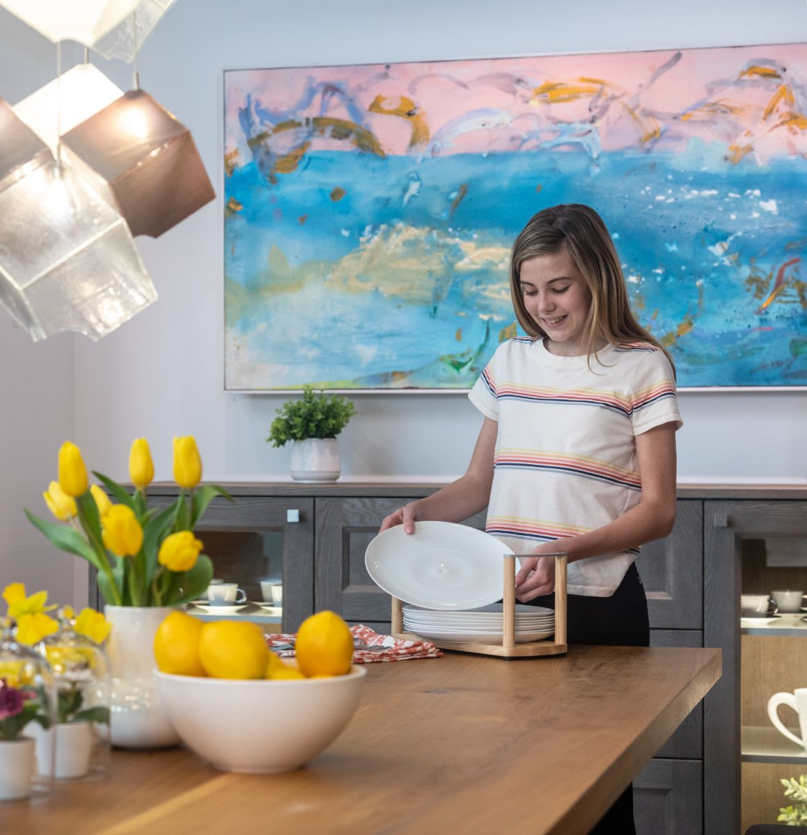 girl sets the table with plates from a boxtec plate caddy that protects plates from sliding while in the drawer and conveniently totes the plates to the table for easy setting