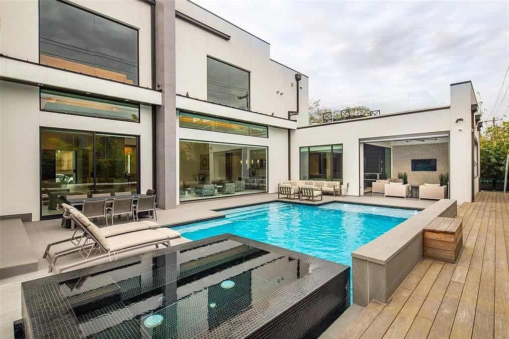 tanglewood homes' expansive backyard deck with pool and outdoor kitchen and lounge