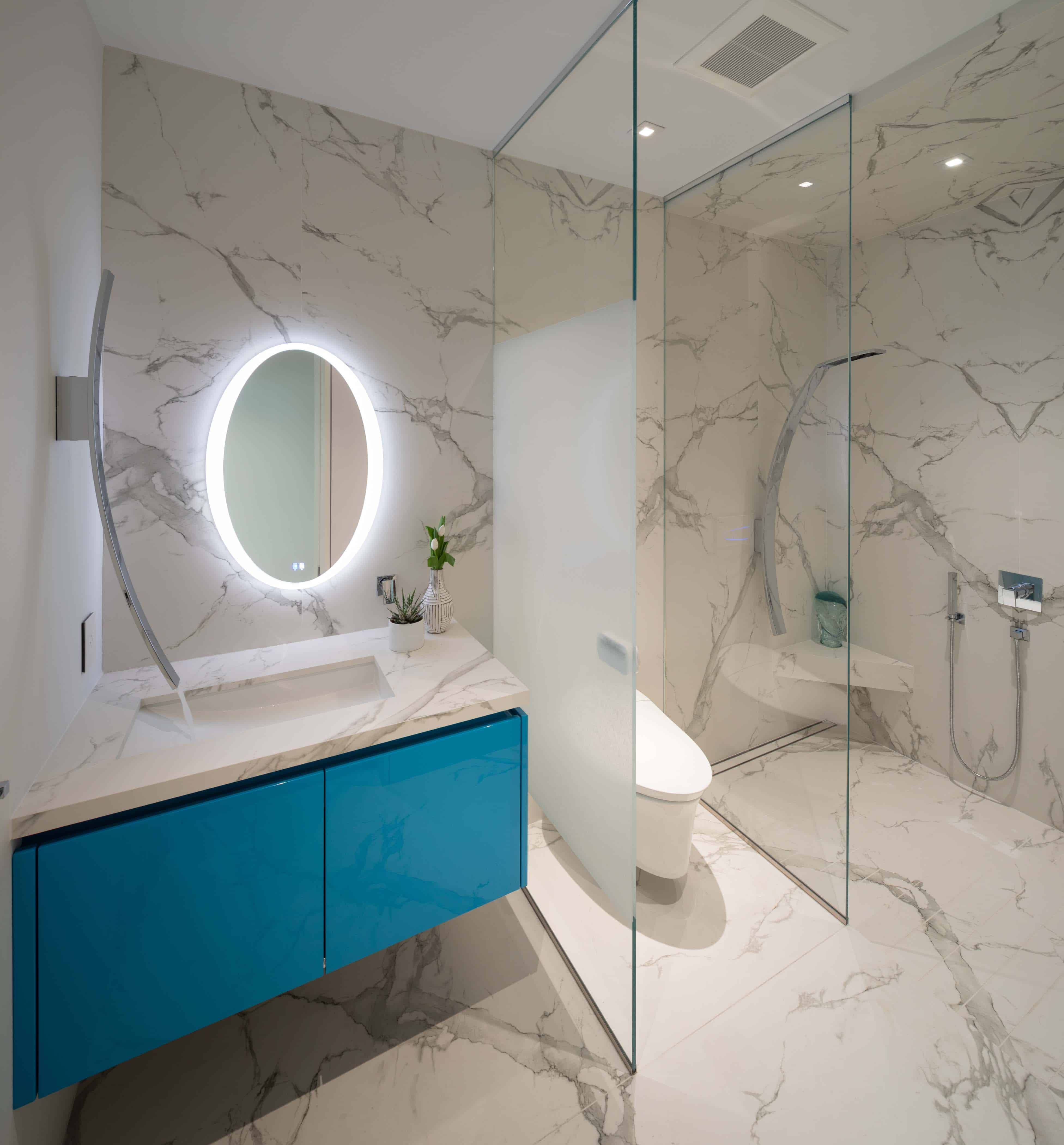 standout turquoise gloss vanity with backlit mirror abuts a water closet and shower with partially sandblasted glass walls in an eggersmann-designed bathroom