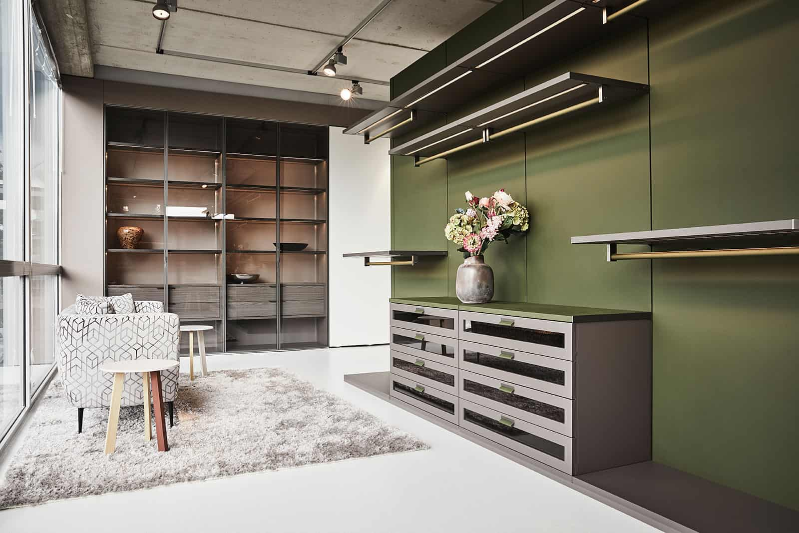 custom luxury walk-in closet with a green accent wall and warm wood touches by schmalenbach designed by eggersmann