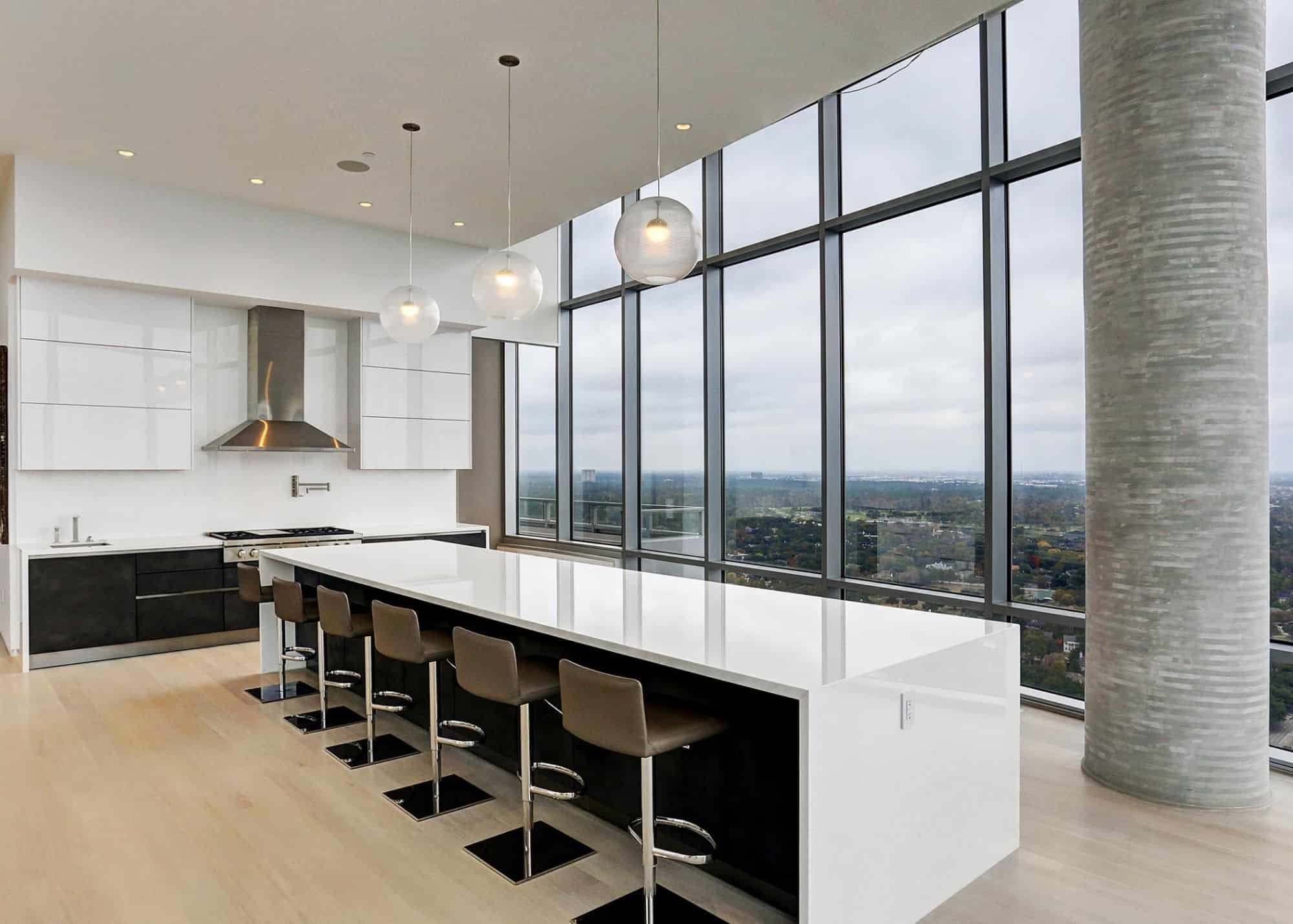 the view inside this ultra-modern glossy white kitchen is just as stunning as the view outside this highrise city apartment