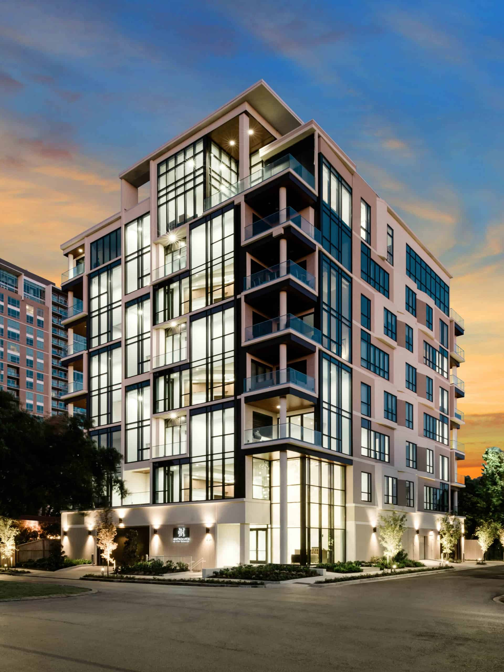 the mondrian luxury apartments in hermann park of houston with a sunset sky in the background