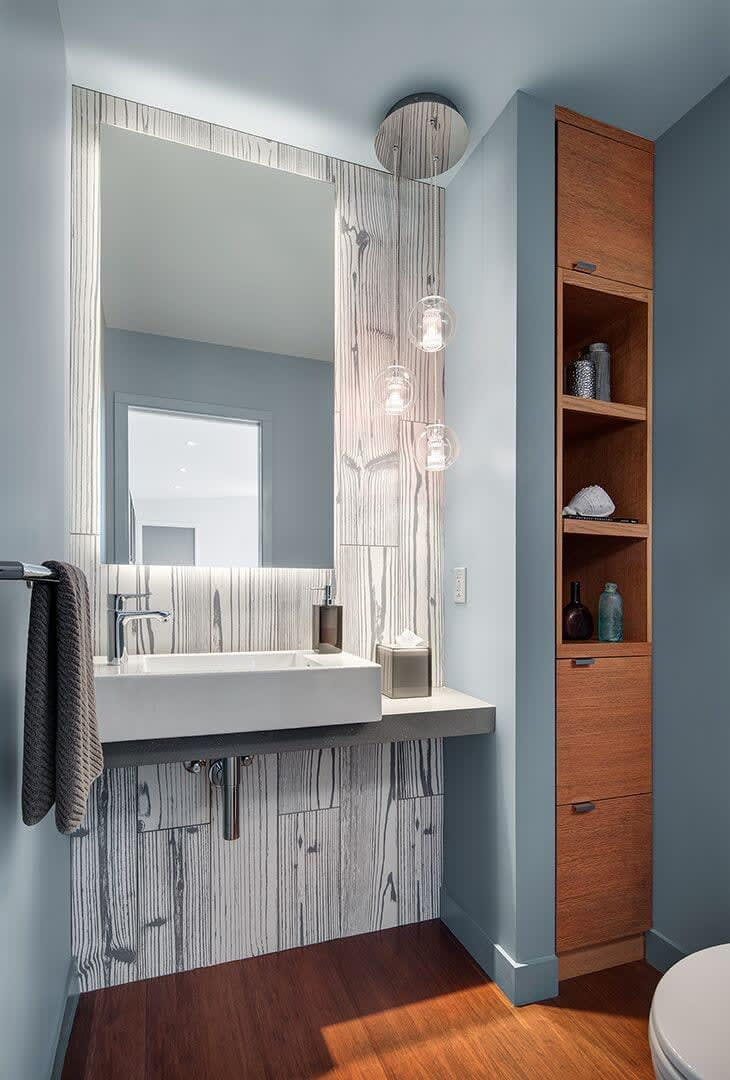 unexpected materials such as a porcelain floor planked tile make a bold statement on the vanity backsplash for this powder room