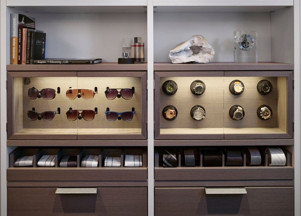 led lighting highlights a luxury closet owner's collection of sunglasses and watches in custom display cabinets