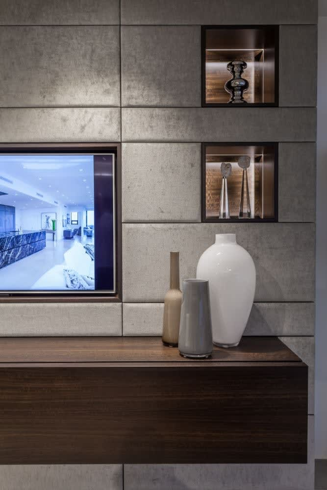 led lighting accents niches in an upholstered media wall designed by eggersmann