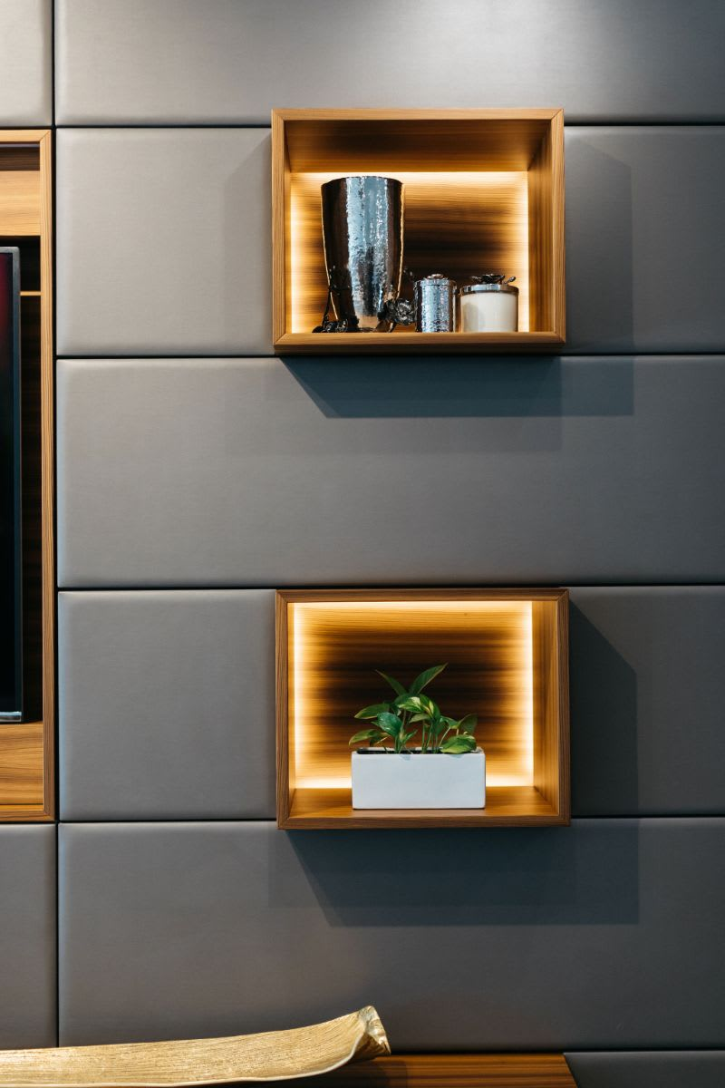 wood cubes on an upholstered media wall with LED backlighting to highlight items on display