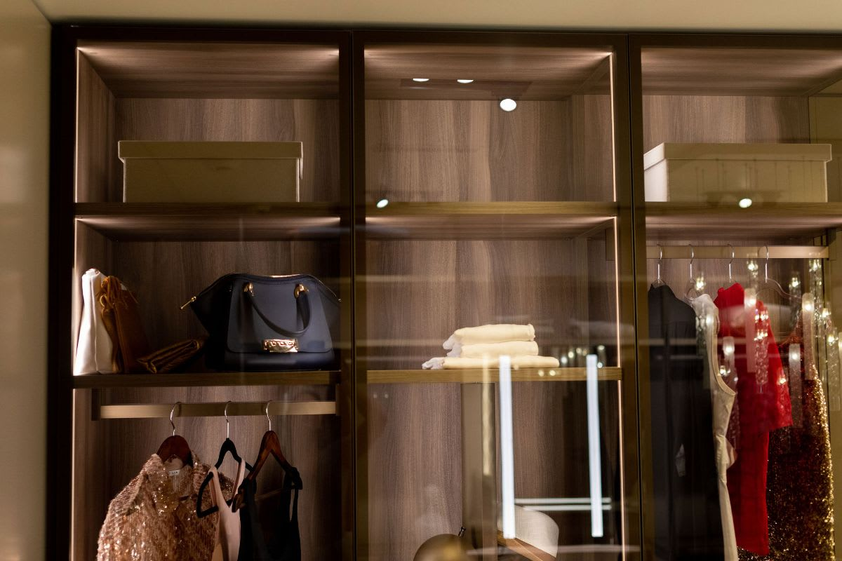 led lighting used inside glass front cabinetry in a luxury walk-in wardrob highlights favorite fashion items