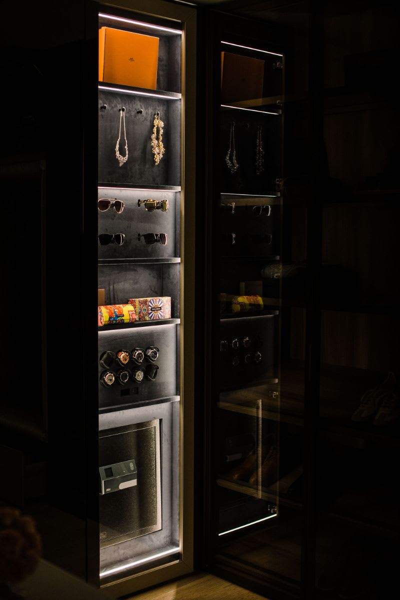 led lighting dramatically highlights cherished jewelry, watches, and other possessions as well as offers a nightlight in this walk-in wardrobe