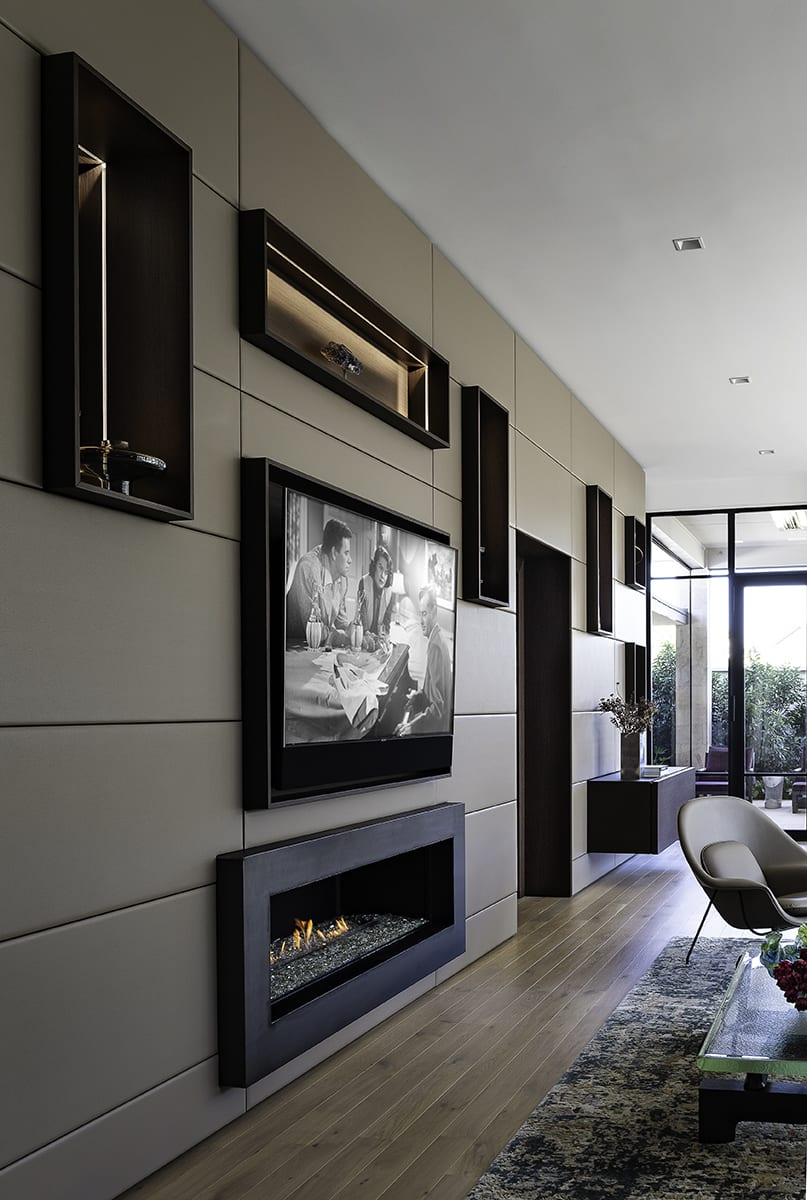 fireplace, tv, niches, and hidden storage in a modular highly functional modern wall of a living area of a southwest contemporary kitchen designed by eggersmann dallas