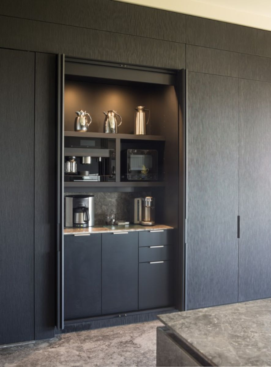 pocket doors on the coffee bar of this luxury modern kitchen
