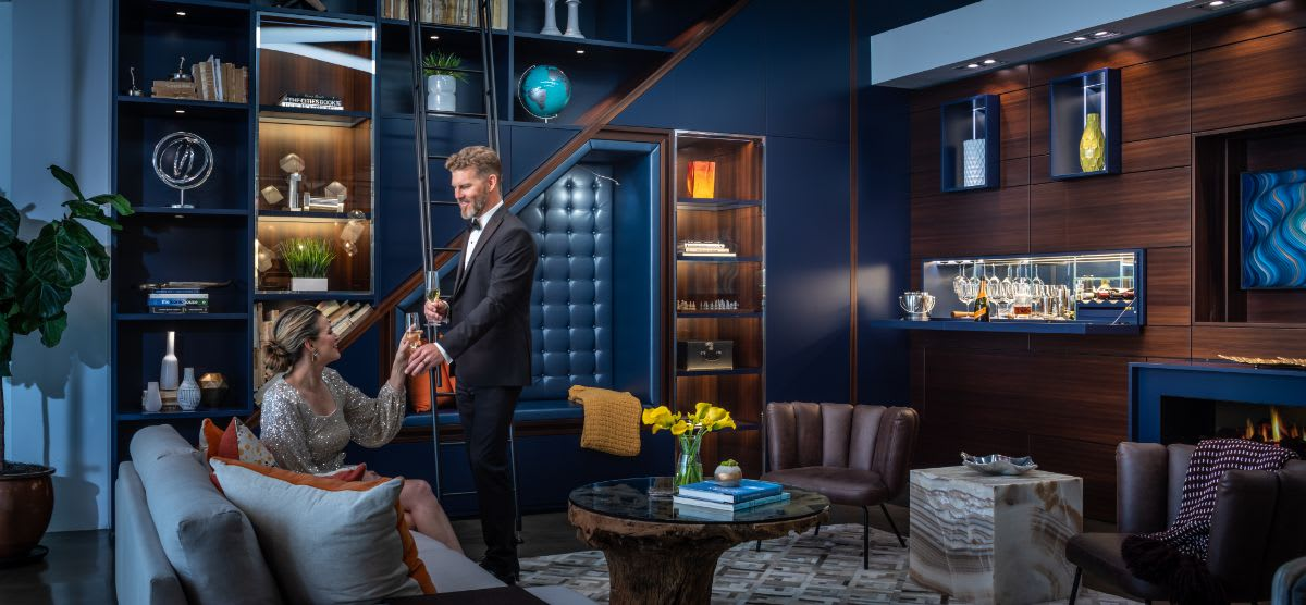 a couple toasting to a romantic evening in an eggersmann-design living area featuring a hidden pull-down bar