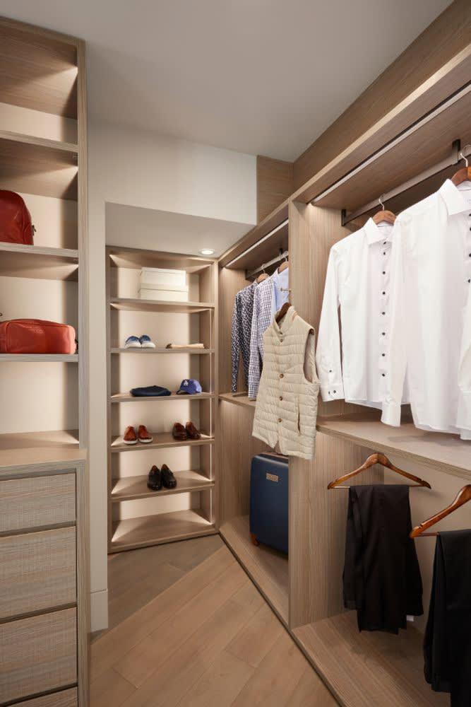 luxury walk-in closet designed by eggersmann in light wood tones
