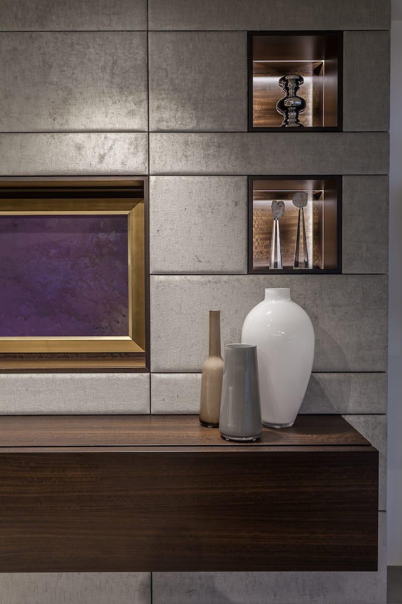 A modern Schmalenbach livingroom design featuring a hidden TV, entertainment center, and veneer display niches.