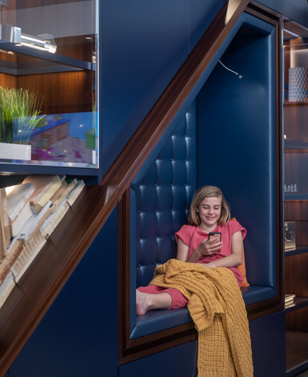 pre-teen girl using phone while seated on a blue tufted leather upholstered seating niche designed by eggersmann using schmalenbach cabinetry components