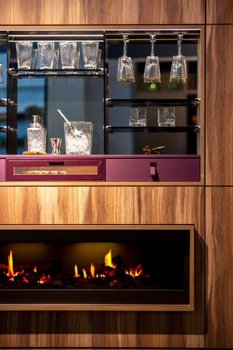 built-in bar above a fireplace in a media wall designed by eggersman with schmalenbach cabinetry components
