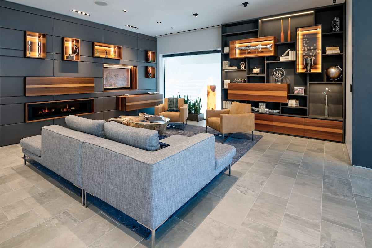 A modern Schmalenbach media unit design featuring a hidden bar, fireplace, and Sophisticated Living furniture.