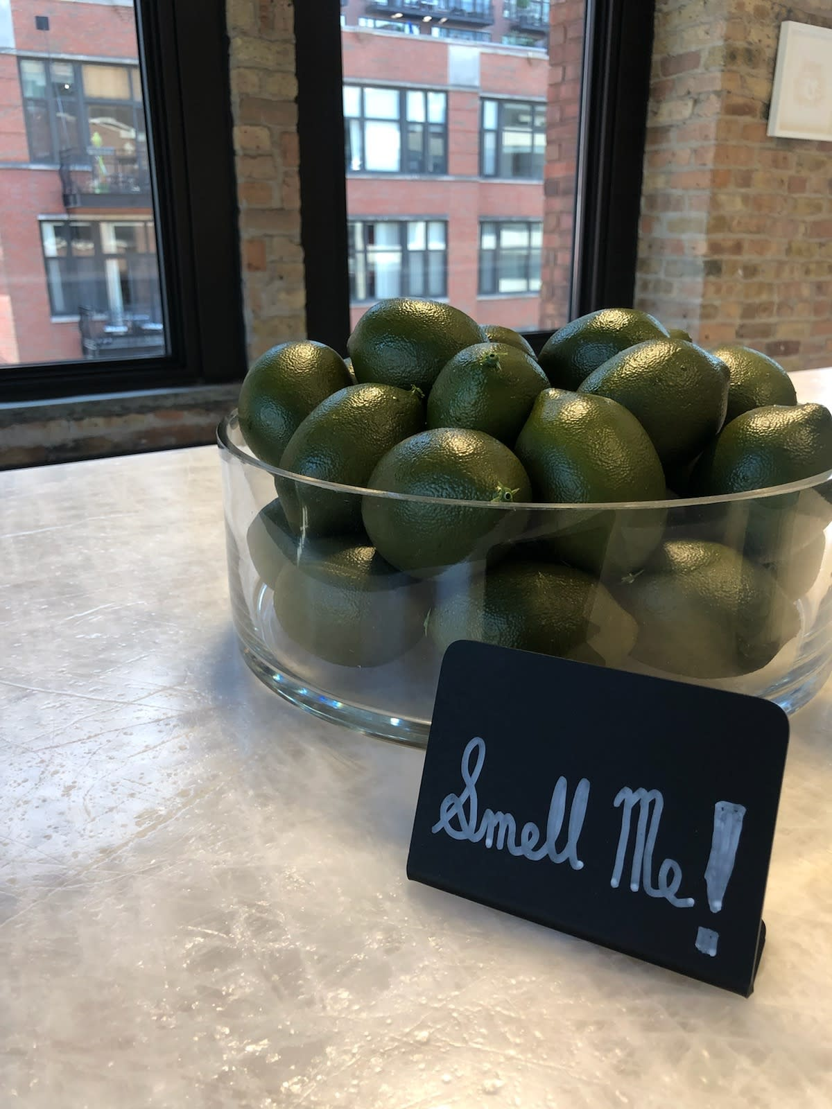 """sign saying """"smell me"""" inviting guests to smell the zest of a bowl of limes"""