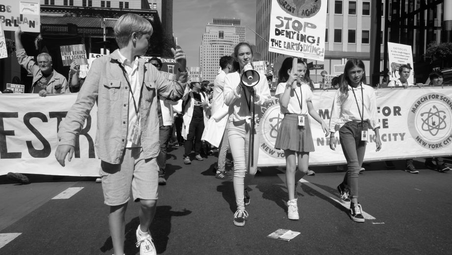 Three young women lead a contingent of scientists in the climate march
